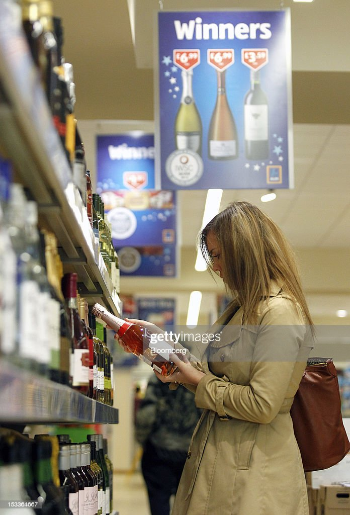 A customer inspects a bottle of sparkling wine on the ''beers, wines & spirits'' aisle at a supermarket operated by Aldi Group, Germany's biggest discount-food retailer, in Manchester, U.K., on Thursday, Oct. 4, 2012. U.K. shop-price inflation slowed in September as retailers offered discounts to attract cash-strapped consumers, the British Retail Consortium said. Photographer: Paul Thomas/Bloomberg via Getty Images