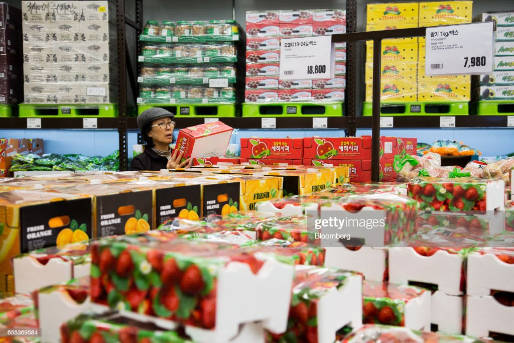 A customer inspects a box of apples at an E-Mart Inc. Traders store in the Starfield Hanam shopping complex, operated by Shinsegae Co., in Hanam, Gyeonggi, South Korea, on Wednesday, March 15, 2017. South Korea is scheduled to release consumer confidence figures on March 24. Photographer: SeongJoon Cho/Bloomberg via Getty Images
