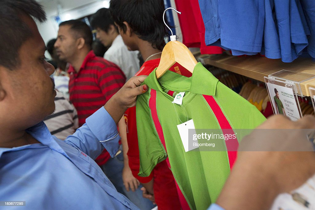 A customer inspects a collared T-shirt at the opening of a Grameen Uniqlo store, a joint venture between Fast Retailing Co. and Grameen Healthcare Trust, in the Paltan area of Dhaka, Bangladesh, on Saturday, Oct. 5, 2013. Fast Retailing, Asia's biggest clothing retailer, set up the venture with Grameen Healthcare Trust to design, make and sell clothes in Bangladesh. Photographer: Jeff Holt/Bloomberg via Getty Images
