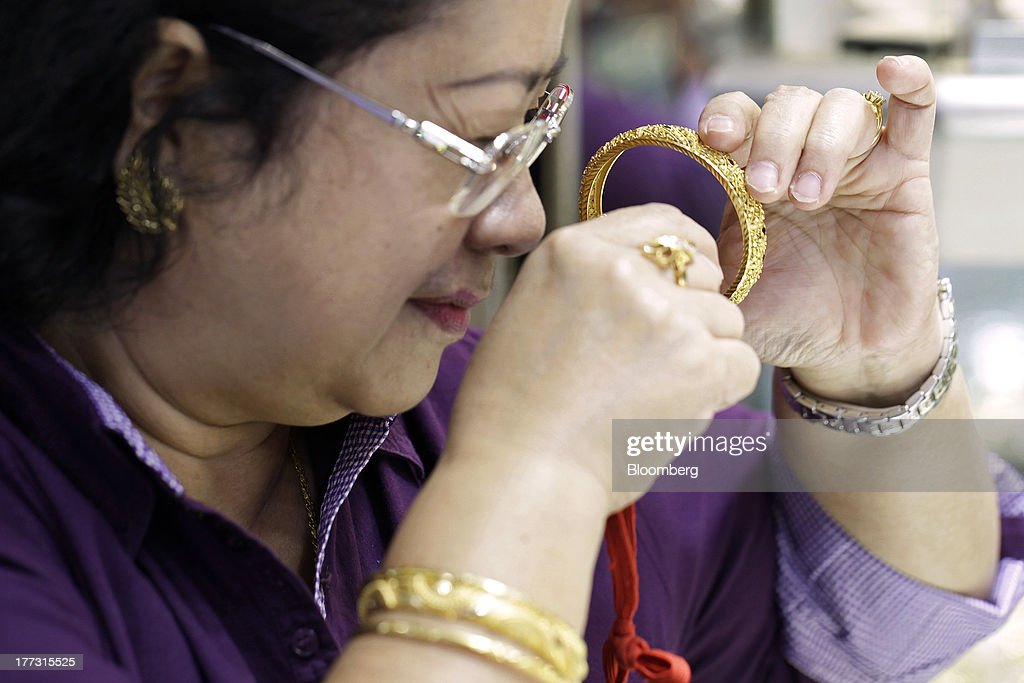 A customer inspects a gold bracelet at a jewelry store in Jakarta, Indonesia, on Thursday, Aug. 22, 2013. Gold jewelry demand in Indonesia is set to expand to a four-year high as consumers in Southeast Asia's biggest buyer join India to China in increasing purchases as prices slump and the middle class expands. Photographer: Dimas Ardian/Bloomberg via Getty Images