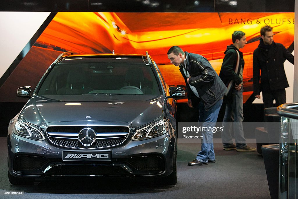 A customer inspects a Mercedes-Benz AMG E63 automobile, produced by Daimler AG, inside the Mercedes-Benz Gallery showroom in Berlin, Germany, on Thursday, Dec. 19, 2013. European new-car sales rose a third consecutive month in November, the longest period of gains in four years. Photographer: Krisztian Bocsi/Bloomberg via Getty Images