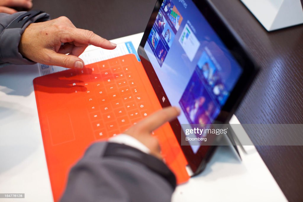 A customer inspects a Microsoft Corp. Surface tablet inside the company's store during its grand opening in New York, U.S., on Thursday, Oct. 25, 2012. Microsoft Corp. introduced the biggest overhaul of its flagship Windows software in two decades, reflecting the rising stakes in its competition with Apple Inc. and Google Inc. for the loyalty of customers who are shunning personal computers and flocking to mobile devices. Photographer: Ramin Talaie/Bloomberg via Getty Images