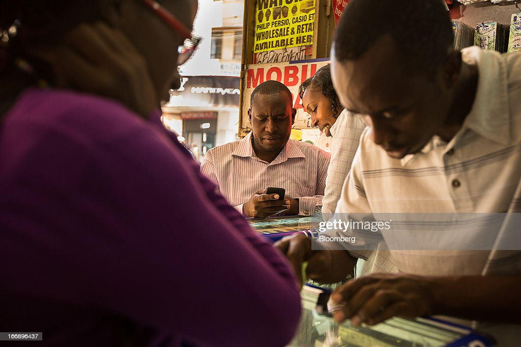 A customer inspects a mobile handset at the counter of a mobile phone store in Nairobi, Kenya, on Wednesday, April 17, 2013. Though only 23 percent of houses there have electricity and just 9 percent of roads are paved, mobile-phone penetration is 75 percent in the country, up from 5 percent in 2003. Photographer: Trevor Snapp/Bloomberg via Getty Images