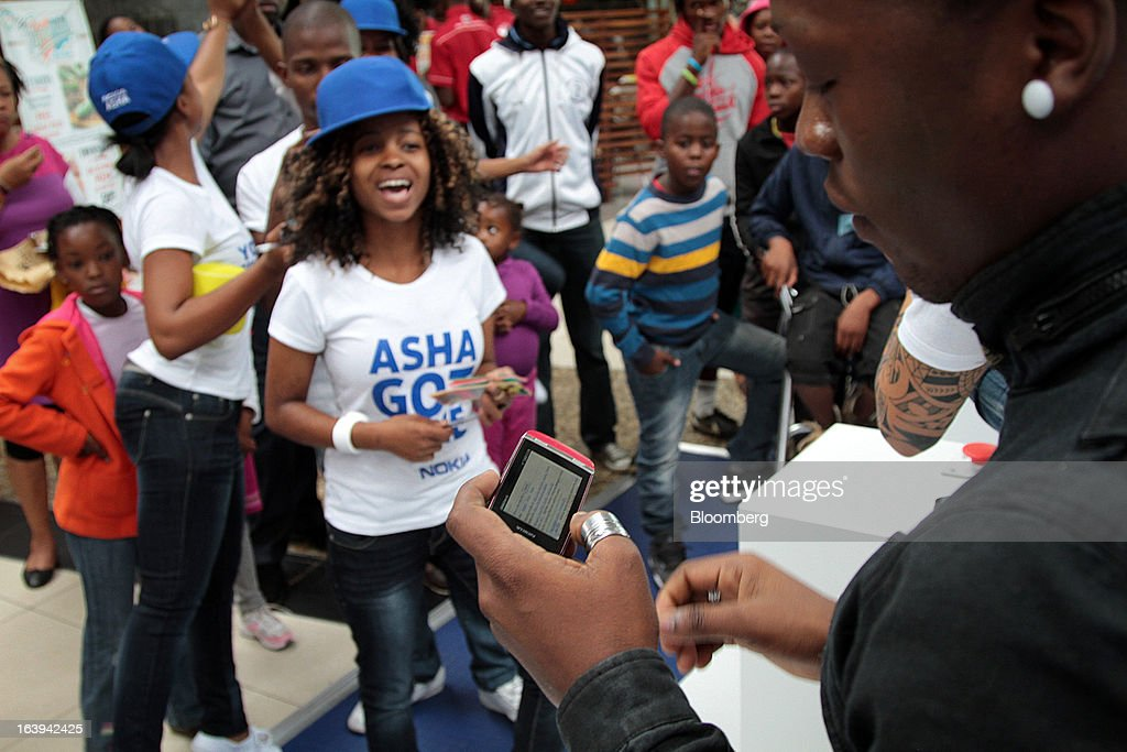 A customer inspects a new Nokia Asha 311 smartphone during a promotional 'activation day' event by Nokia Oyj in Maponya Mall in Soweto, South Africa, on Saturday, March 16, 2013. Nokia, based in Espoo, Finland, introduced three phones for its Asha line, sold primarily in emerging markets. Photographer: Nadine Hutton/Bloomberg via Getty Images
