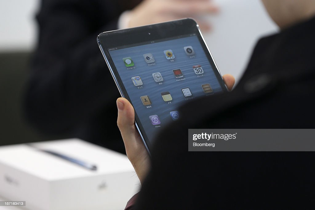 A customer inspects a newly purchased Apple Inc. iPad Mini at a KDDI Corp. store in Tokyo, Japan, on Friday, Nov. 30, 2012. The iPad Mini went on sale at KDDI and Softbank Corp. stores in Japan today. Photographer: Kiyoshi Ota/Bloomberg via Getty Images