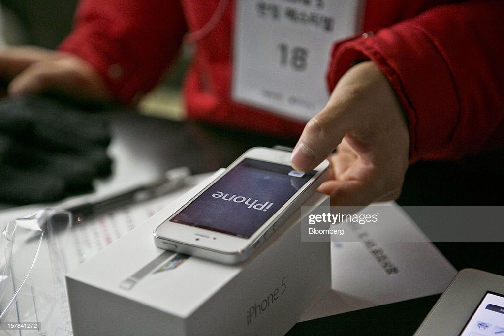 A customer inspects a newly unboxed Apple Inc. iPhone 5 at a KT Corp. Olleh brand mobile phone store in Seoul, South Korea, on Friday, Dec. 7, 2012. The iPhone 5 went on sale in South Korea today. Photographer: Jean Chung/Bloomberg via Getty Images