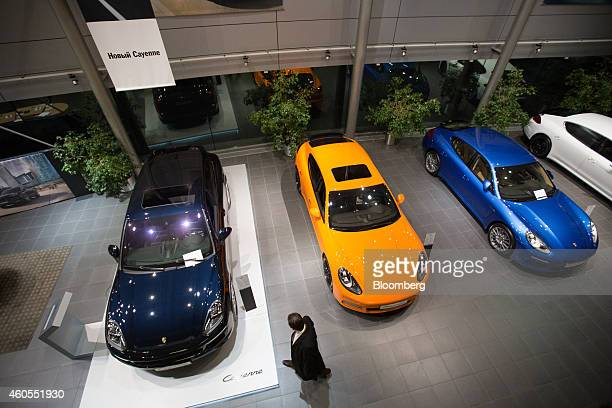 A customer inspects a Porsche Cayenne left vehicle as it stands for sale inside a Porsche AG new automobile dealership in Moscow Russia on Monday Dec...