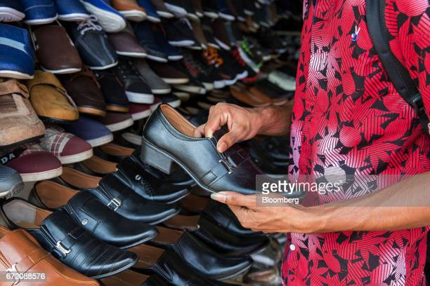 A customer inspects a shoe at a store in the Pettah neighborhood of Colombo Sri Lanka on Thursday April 20 2017 The Central Bank of Sri Lanka is...