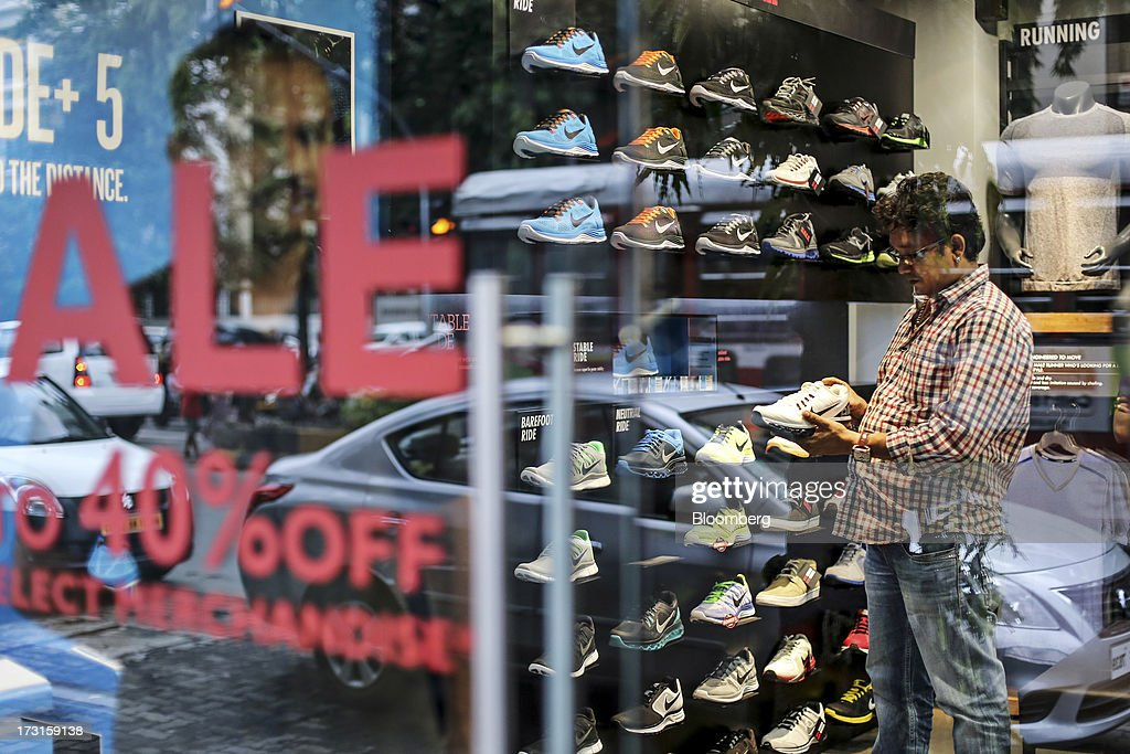 A customer inspects a sports shoe in a Nike Inc. store advertising a sale in the suburb of Bandra in Mumbai, India, on Saturday, July 6, 2013. India's consumer price index (CPI) figures for June are scheduled to be released on July 12. Photographer: Dhiraj Singh/Bloomberg via Getty Images