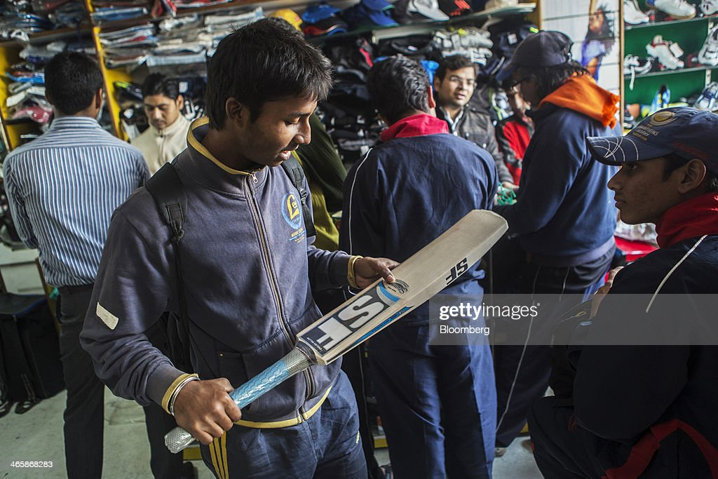 A customer inspects a Stanford Cricket Industries cricket bat at a sports store in Meerut, Uttar Pradesh, India, on Wednesday, Jan. 29, 2014. The Indian Premier League (IPL), the worlds richest cricket competition, auction for IPL 2014 is scheduled to begin on Feb. 12 with the seasons first match to be played on April 8. Photographer: Prashanth Vishwanathan/Bloomberg via Getty Images
