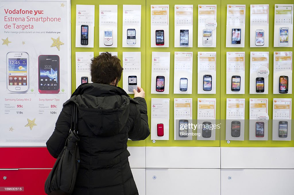 A customer inspects a Vodafone 555 Blue mobile handset from a display of smartphones inside a Vodafone Group Plc store in Barcelona, Spain, on Tuesday, Jan. 15, 2013. Vodafone Group Plc, the world's second largest mobile-phone company, plans to reduce the workforce at its Spanish unit as unemployment exceeding 25 percent in the recession-plagued country causes sales to drop. Photographer: David Ramos/Bloomberg via Getty Images