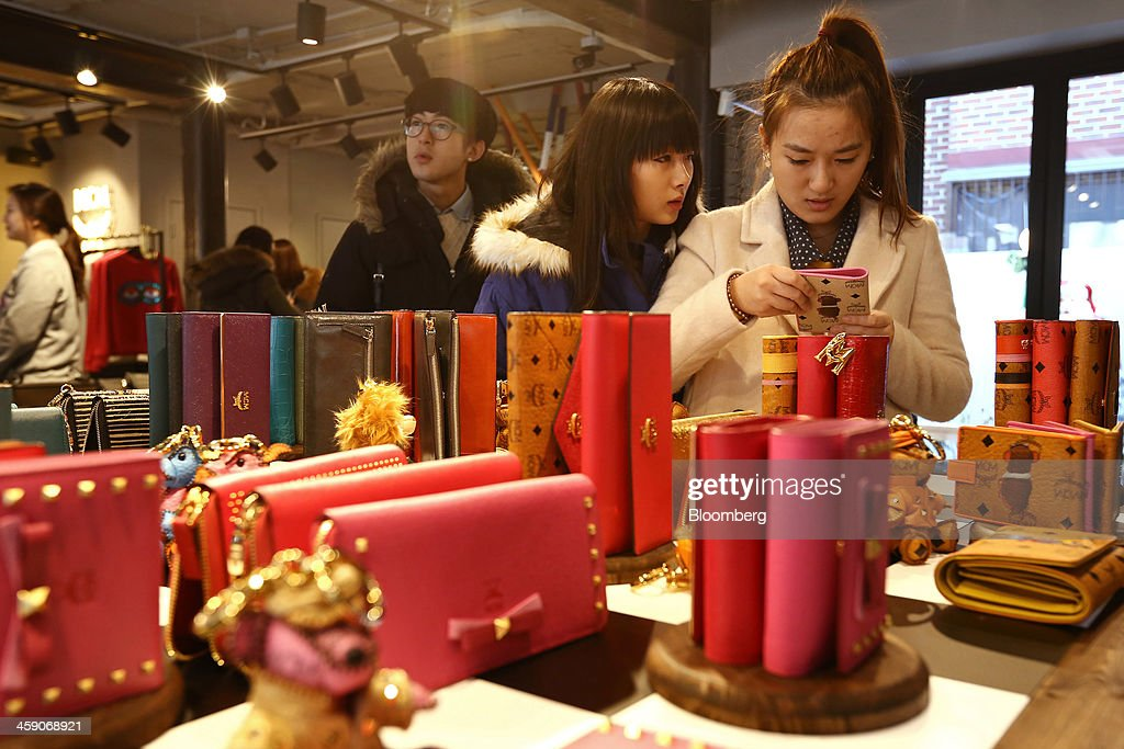 A customer inspects a wallet inside an MCM Holdings AG store on Garosugil street in the Gangnam district of Seoul, South Korea, on Sunday, Dec. 22, 2013. Consumer prices climbed 0.9 percent in November from a year earlier after a 0.7 percent increase in October that was the smallest gain since July 1999. Photographer: SeongJoon Cho/Bloomberg via Getty Images
