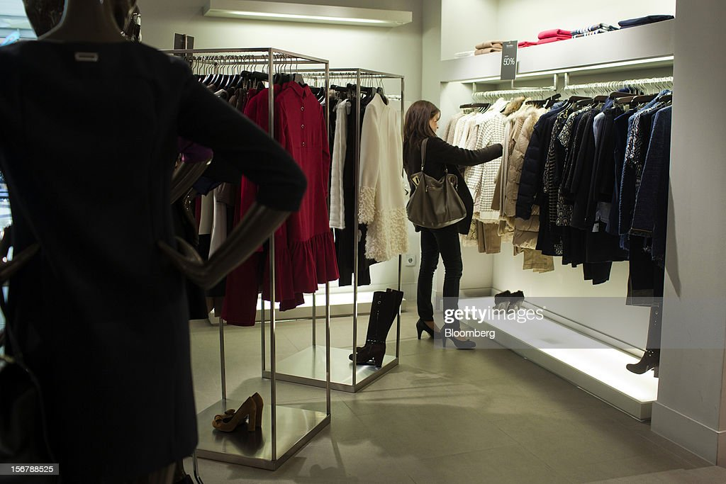 A customer inspects discounted women's garments hanging from a rail in a Cortefiel SA store in Majadahonda, near Madrid, Spain, on Tuesday, Nov. 20, 2012. Bank of Spain Governor Luis Maria Linde said the government risks missing its budget targets this year and next, adding to doubts on Prime Minister Mariano Rajoy's ability to cut the deficit amid a five-year slump. Photographer: Angel Navarrete/Bloomberg via Getty Images