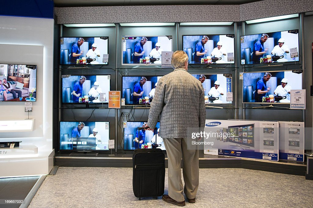 A customer inspects flat screen televisions for sale inside an El Corte Ingles SA department store in Barcelona, Spain, on Thursday, May 30, 2013. Spain's recession eased in the first quarter as domestic demand stabilized while exports, which the government says will drive the recovery of the euro-area's fourth-largest economy, fell at the fastest pace in a year. Photographer: David Ramos/Bloomberg via Getty Images
