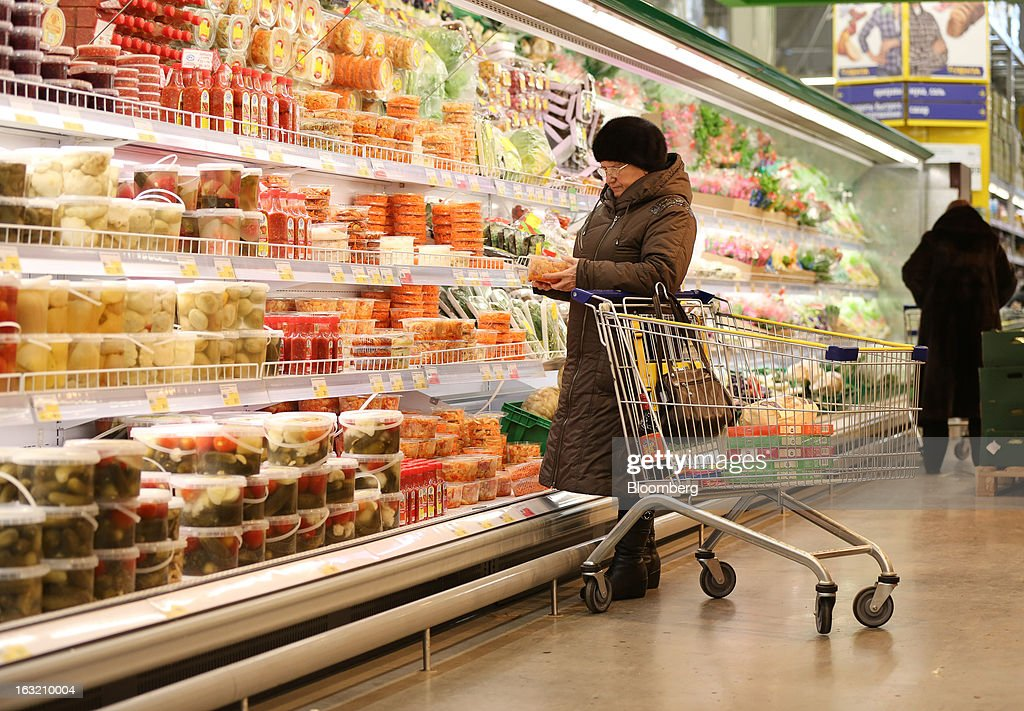 A customer inspects food from a chilled cabinet of pickled goods inside a Lenta LLC supermarket in Prokopyevsk, Kemerevo region, Russia, on Wednesday, March 6, 2013. Lenta LLC, a Russian hypermarket operator controlled by TPG Capital, is selling its first bond to expand after using company funds for a leveraged buyout by the U.S. firm. Photographer: Andrey Rudakov/Bloomberg via Getty Images
