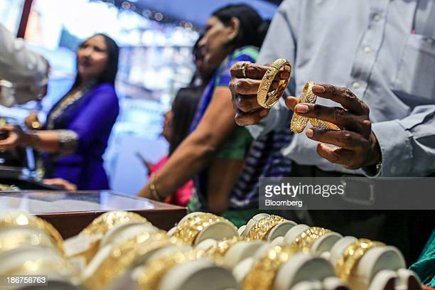A customer inspects gold bangles at the Umedmal Tilokchand Zaveri jewelry store during the festival of Dhanteras two days before Diwali in the Zaveri...