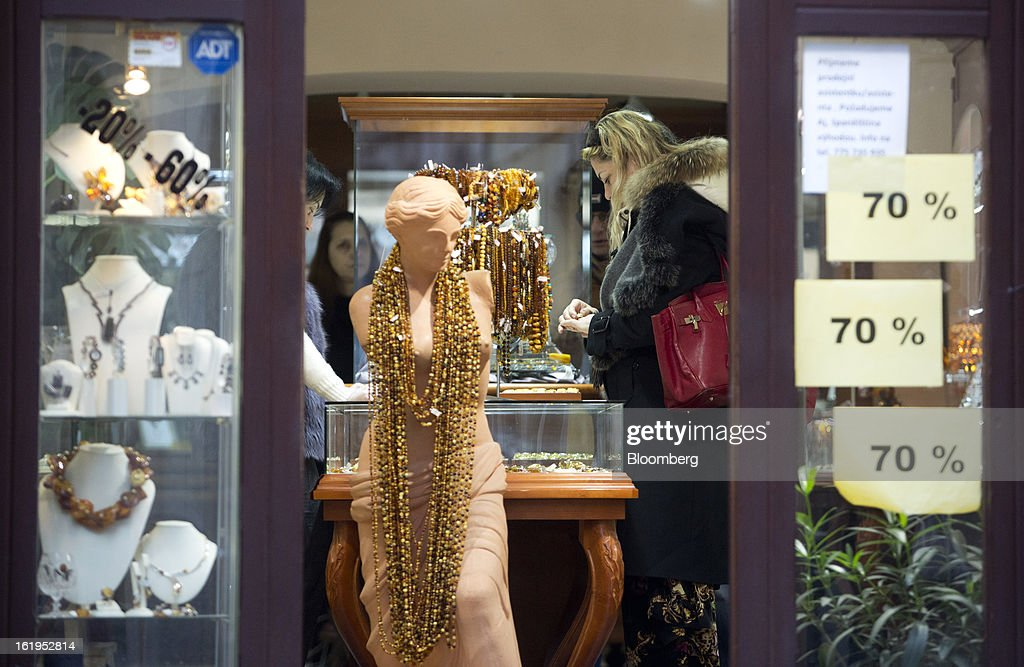 A customer inspects jewelry in a store advertising 70 percent discounts in its windows in Prague, Czech Republic, on Sunday, Feb. 17, 2013. Worsened outlook for Czech economy is in line with the government's expectations and lower-than-planned tax revenue is 'manageable' under 2013 budget, Prime Minister Petr Necas said on Czech public television. Photographer: Martin Divisek/Bloomberg via Getty Images