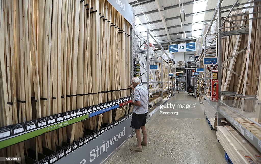 A customer inspects lengths of timber inside a B&Q home improvement store, operated by Kingfisher Plc, in London, U.K., on Tuesday, July 16, 2013. Financial assistance for first-time home buyers in Britain is likely to prompt a resurgence of do-it-yourself spending after several years of decline, according to Kingfisher Plc Chief Executive Officer Ian Cheshire. Photographer: Chris Ratcliffe/Bloomberg via Getty Images