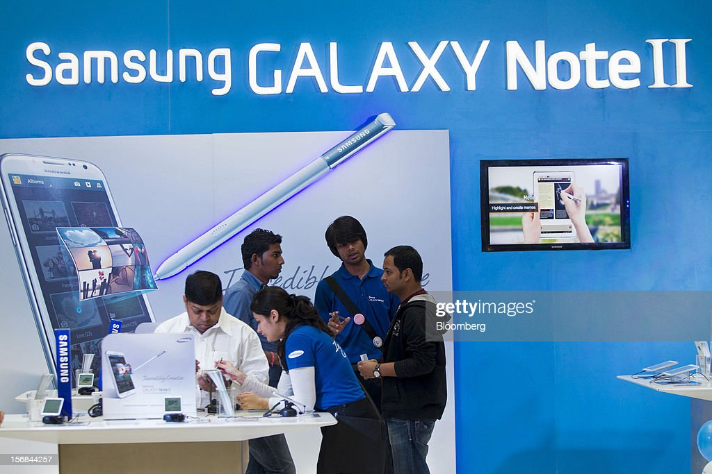 A customer inspects mobile devices at a kiosk selling Samsung Electronics Co. products in Ambience Mall in Gurgaon, India, on Wednesday, Nov. 21, 2012. Indian Prime Minister Manmohan Singh aims to spur spending on infrastructure to revive a faltering economy and tackle bottlenecks contributing to one of Asia's highest inflation rates. Photographer: Brent Lewin/Bloomberg via Getty Images
