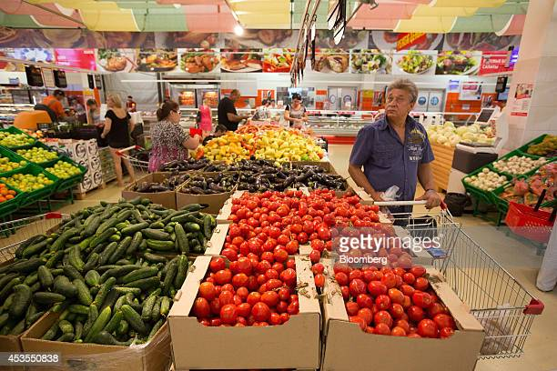 A customer inspects ruble price signs for fruit and vegetables inside an OAO Magnit hypermarket in Krasnodar Russia on Thursday Aug 7 2014 Russia...