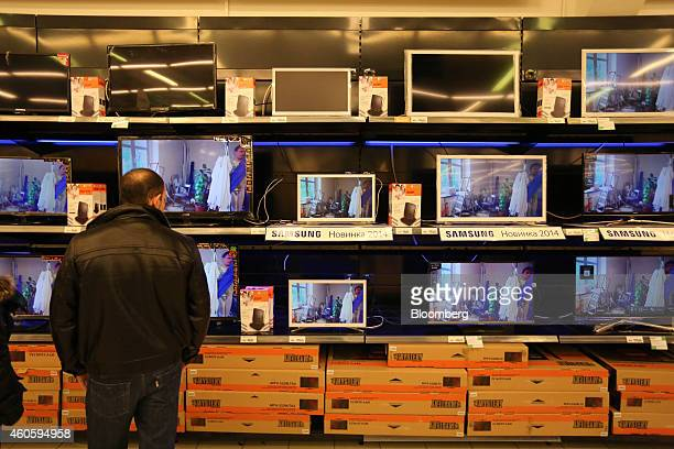 A customer inspects Samsung Electronics Co flatscreen televisions for sale inside an O'Key hypermarket in Saint Petersburg Russia on Wednesday Dec 17...
