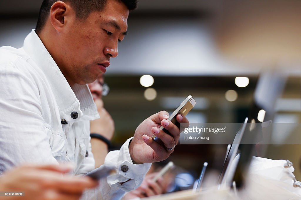 A customer inspects the new iPhone at the Wangfujing flagship store on September 20, 2013 in Beijing, China. Apple launched the new iPhone 5C model that will run iOS 7 is made from hard-coated polycarbonate and comes in various colors and the iPhone 5S that features fingerprint recognition security.