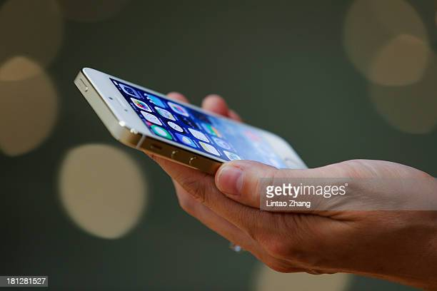 A customer inspects the new iPhone at the Wangfujing flagship store on September 20 2013 in Beijing China Apple launched the new iPhone 5C model that...