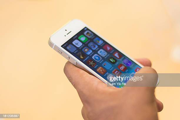 A customer inspects the new iPhone inside Apple's store in Causeway Bay district on September 20 2013 in Hong Kong China Hong Kong was one of the...