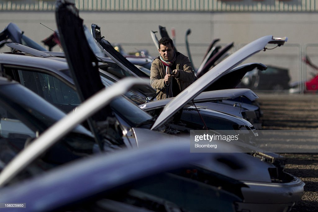 A customer inspects windscreen wiper blades while checking for spare parts on a scrapped automobile in the yard of the Desguaces La Torre scrapyard in Madrid, Spain, on Thursday, Dec. 13, 2012. Spain has completed the debt sales it planned for this year and started raising funds for 2013, buying time for Prime Minister Mariano Rajoy as he decides whether to seek a European bailout. Photographer: Angel Navarrete/Bloomberg via Getty Images