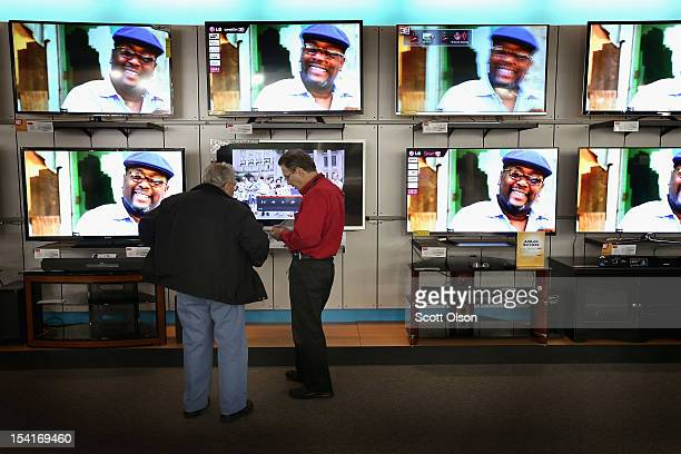 A customer is helped as he looks over televisions being offered for sale at an hhgregg store on October 15 2012 in Niles Illinois Retail sales rose...