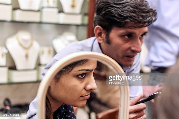 A customer is reflected in a mirror as she listens to a salesperson at the Dwarkadas Chandumal Jewelers store during the festival of Dhanteras two...