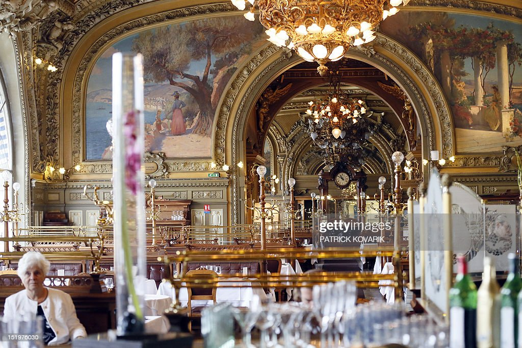 """A customer is seated in the main room of the 'Train Bleu' restaurant, on September 14, 2012 at the Gare de Lyon in Paris. The restaurant, initially called """"Buffet de la Gare de Lyon"""" was built upon the occasion of the Universal Exhibition in 1900 by the Paris-Lyon-Mediterranean (PLM) Company and was granted historical monument status in 1972 by former Minister Andre Malraux."""