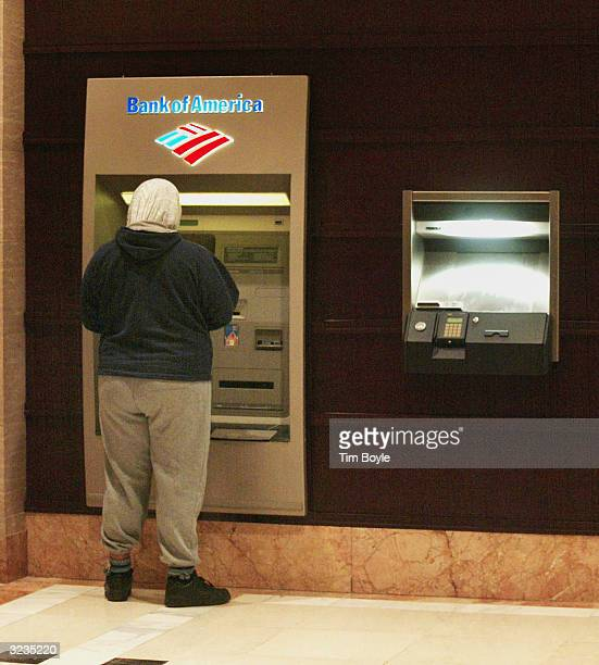 A customer is seen at an ATM inside the Bank of America building April 6 2004 in Chicago Charlotte North Carolinabased Bank of America has said it...