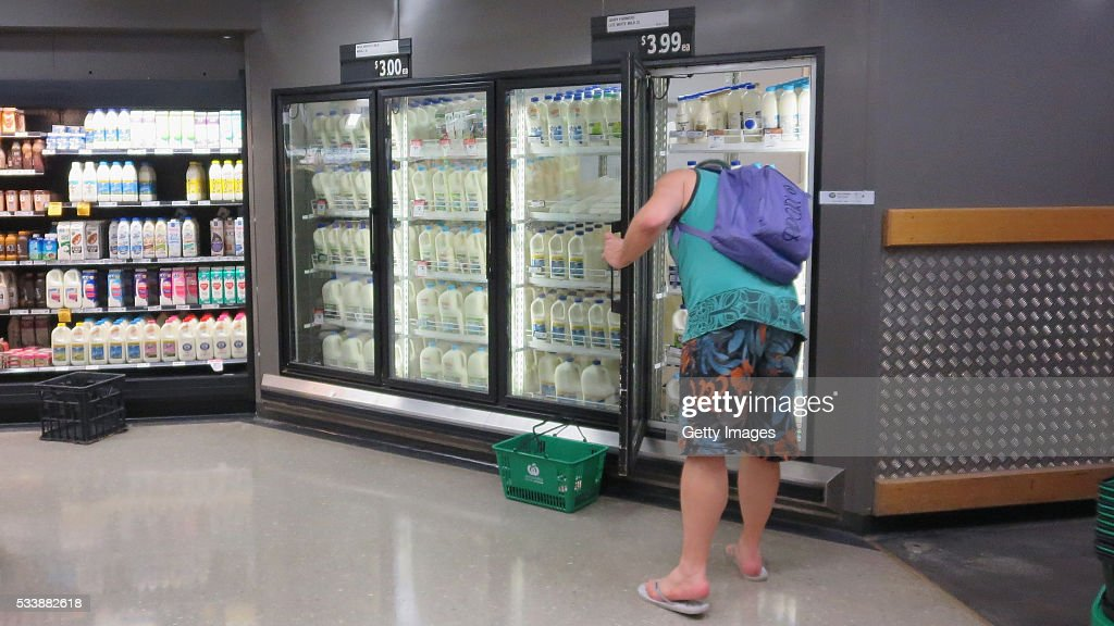 A customer is seen purchasing milk in a Woolworths supermarket on May 24, 2016 in Sydney, Australia. Australians are rallying around it's dairy farmers by opting to purchase branded milk rather than the cheaper store brands after the country's largest dairy company Murray Goulburn last month cut the price it pays suppliers by 15%.