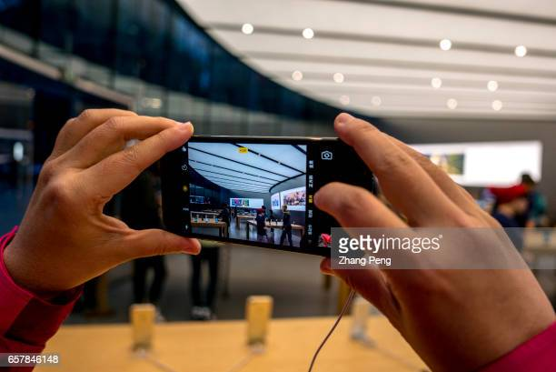 A customer is trying an iPhone 7 in the apple shop On the March 25 Apple opened the third retail shop in Nanjing city which is located in Nanjing...