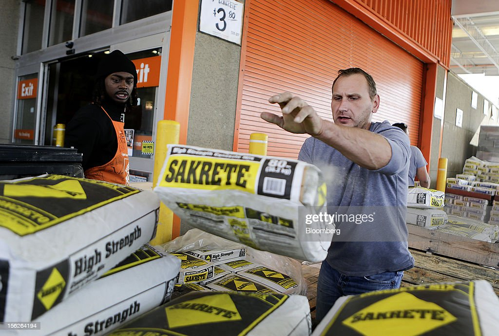Customer Jacek Mroczkowski, right, tosses a Sakrete concrete mix bag into his truck at a Home Depot Inc. store in Washington, D.C., U.S., on Monday, Nov. 12, 2012. Home Depot Inc. is scheduled to release earnings data on Nov. 13. Photographer: Andrew Harrer/Bloomberg via Getty Images