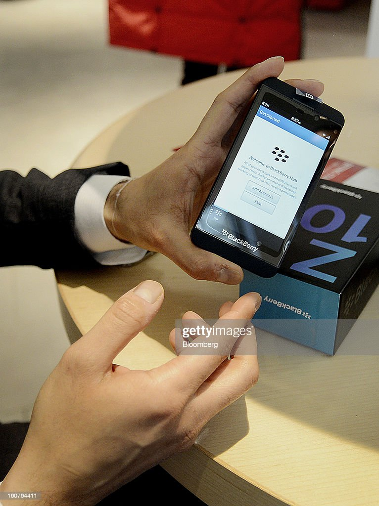"Customer Jay Charnalia displays his new Blackberry Z10 device for a photograph on the first day of sales at a Rogers Communications Inc. store in Toronto, Ontario, Canada, on Tuesday, Feb. 5, 2013. Thorsten Heins, president and chief executive officer of BlackBerry, said early sales of the Z10 smartphone are ""encouraging"" and that users are switching from other platforms. Photographer: Aaron Harris/Bloomberg via Getty Images"
