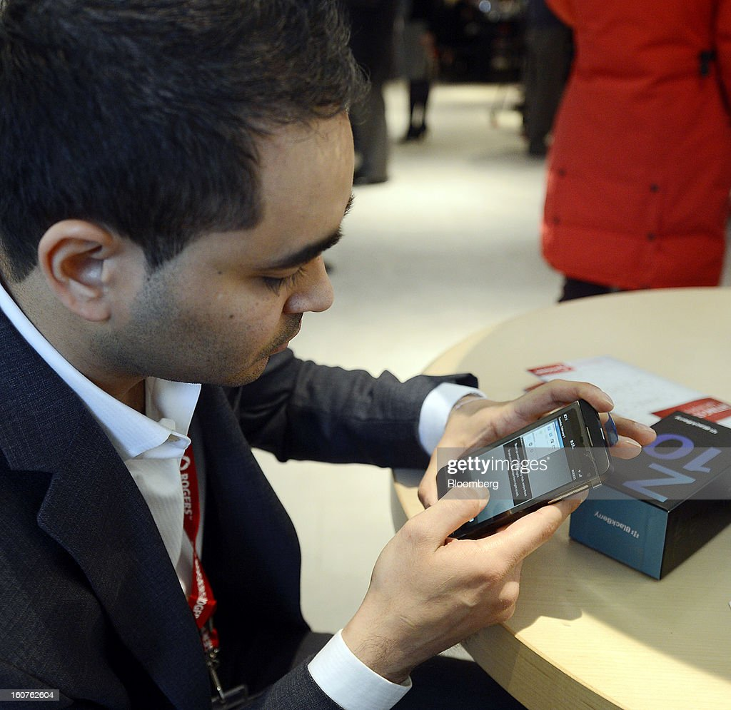 "Customer Jay Charnalia sets up his new Blackberry Z10 device on the first day of sales at a Rogers Communications Inc. store in Toronto, Ontario, Canada, on Tuesday, Feb. 5, 2013. Thorsten Heins, president and chief executive officer of BlackBerry, said early sales of the Z10 smartphone are ""encouraging"" and that users are switching from other platforms. Photographer: Aaron Harris/Bloomberg via Getty Images"