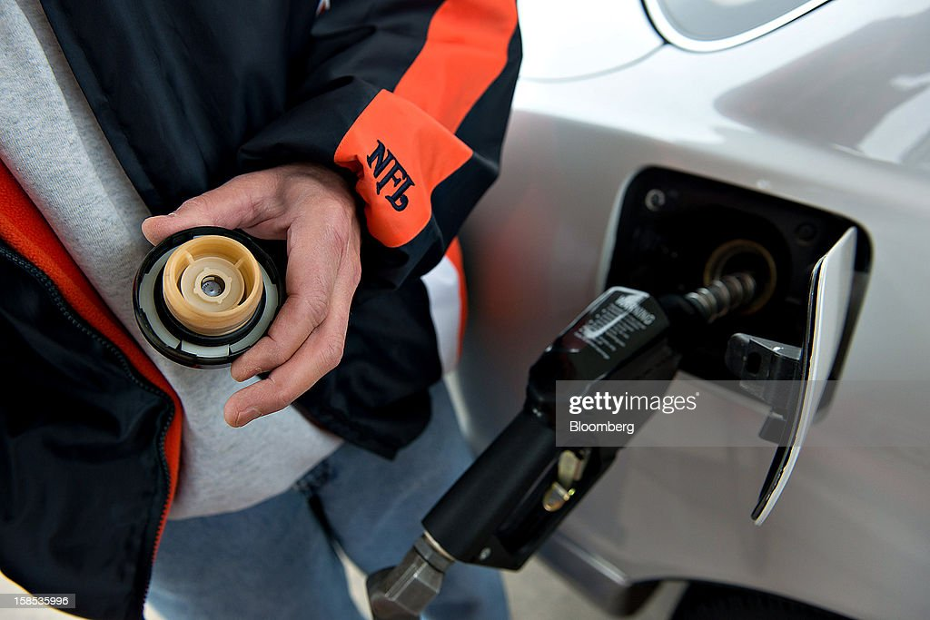 Customer Jerry Johnson holds his gas cap as he pumps fuel into his car at a gas station in Princeton, Illinois, U.S., on Tuesday, Dec. 18, 2012. Retail gasoline in the U.S. fell to the lowest level in a year as refineries restored production and stockpiles rose to an eight-month high, blunting criticism of President Barack Obama's energy policies. Photographer: Daniel Acker/Bloomberg via Getty Images
