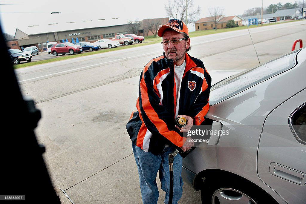 Customer Jerry Johnson pumps fuel into his car at a gas station in Princeton, Illinois, U.S., on Tuesday, Dec. 18, 2012. Retail gasoline in the U.S. fell to the lowest level in a year as refineries restored production and stockpiles rose to an eight-month high, blunting criticism of President Barack Obama's energy policies. Photographer: Daniel Acker/Bloomberg via Getty Images