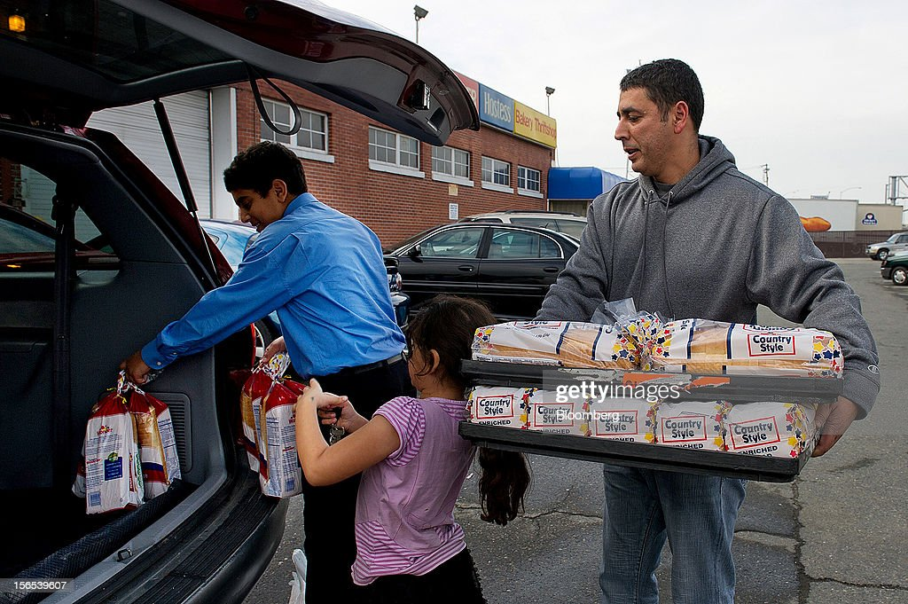 Customer Kamal Moharam, right, gets help from his daughter Nadine, 7, center, and son Kareem, 13, loading their car with Hostess Brands Inc. Wonder Bread at the company's bakery outlet in Sacramento, California, U.S., on Friday, Nov. 16, 2012. Hostess, which also makes Wonder bread, Ding Dongs and Ho Hos, plans to fire more than 18,000 employees and liquidate assets after a nationwide strike by bakery workers crippled operations. Photographer: David Paul Morris/Bloomberg via Getty Images