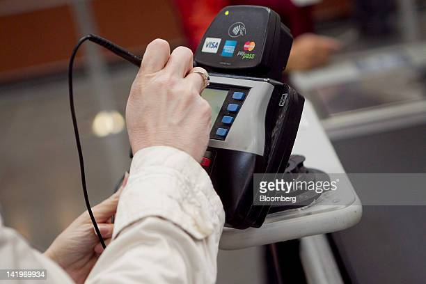 Customer Kelly Murray signs her name on a credit card machine while checking out at a BJ's Wholesale Club Inc store in Falls Church Virginia US on...