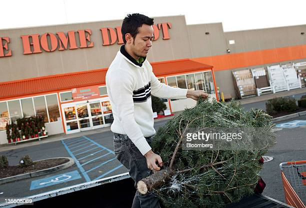 Customer Kelvin Kikuthi loads a Christmas tree into the bed of his truck at a Home Depot Inc store in Newark New Jersey US on Saturday Dec 10 2011...