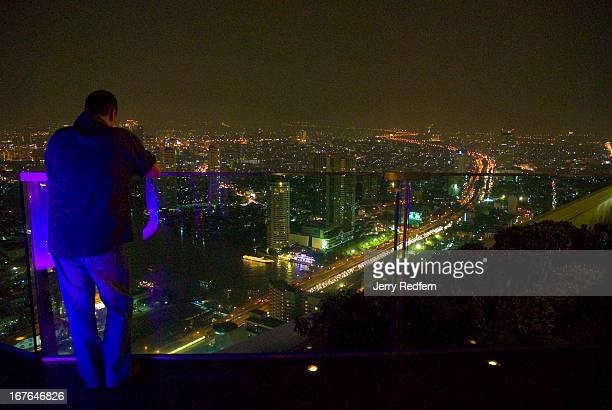 A customer leans against the glass railing at the SkyBar at Sirocco restaurant atop the State Building in Bangkok