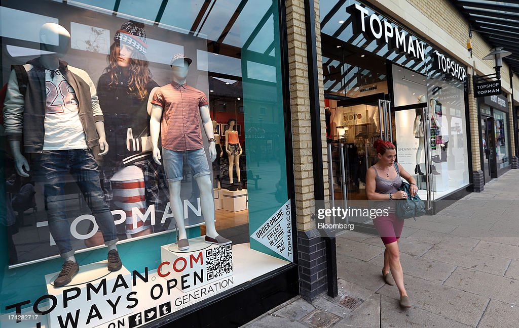A customer leaves a branch of Topman and Topshop, operated by Arcadia Group Ltd., in Hastings, U.K., on Tuesday, July 23, 2013. U.K. retail sales rose for a second month in June as discounts at department stores drove demand for clothes and electrical products. Photographer: Chris Ratcliffe/Bloomberg via Getty Images