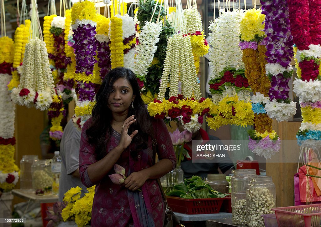 A customer leaves a flower shop after buying Lotus in the Brickfields area, also known as Little India, in Kuala Lumpur on November 20, 2012. Malaysia's economy grew a better-than-expected 5.2 percent in the third quarter as domestic demand continued to compensate for a slowdown in exports, the government said recently. AFP PHOTO / Saeed KHAN