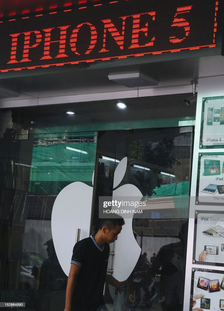 A customer leaves a shop selling Apple products with a digital advertising display announcing that Apple's smart phone Iphone 5 is available for sale on a street in downtown Hanoi on September 28, 2012. Not being among themarkets choosen for Apple's inaugural sale of the Iphone 5, Vietnam's smart phone market gets feverish with hi-tech lovers and wealthy people ready to pay up to 23 million dongs or 1,100 USD for an Iphone 5 16G model, all of which are imported by individuals from Singapore, Hongkong or the US. AFP PHOTO/HOANG DINH Nam