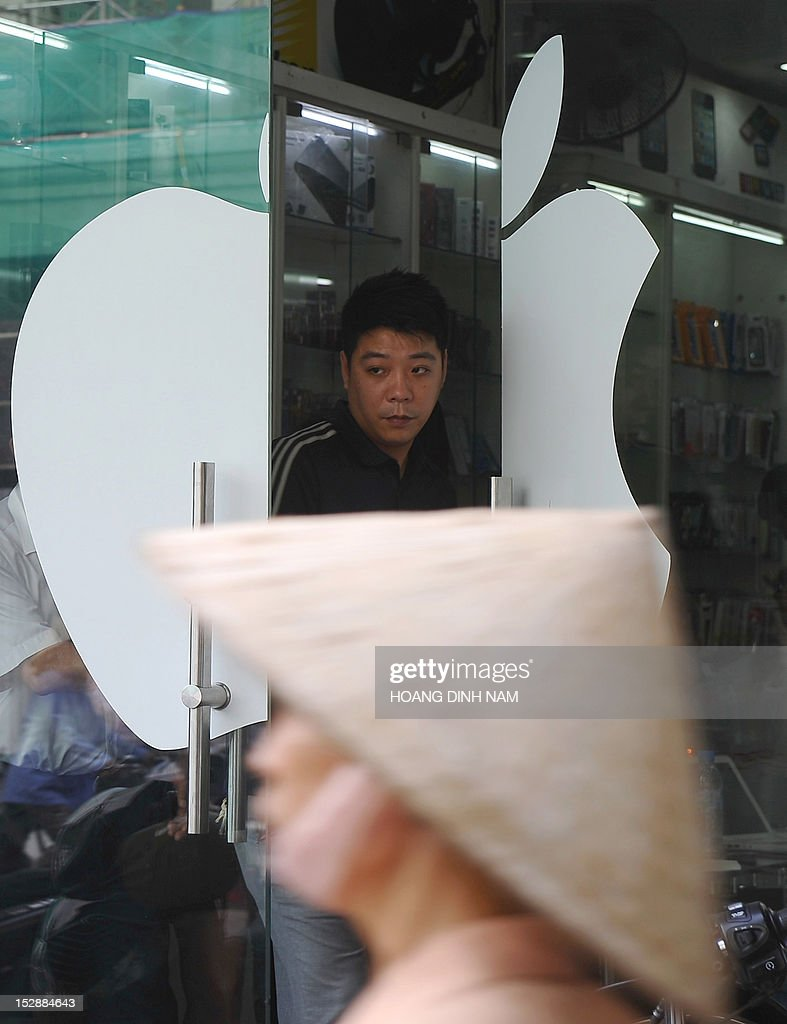 A customer leaves a shop selling Apple products with a digital advertising display announcing that Apple's smart phone Iphone 5 is available for sale on a street in downtown Hanoi on September 28, 2012. Not being among themarkets choosen for Apple's inaugural sale of the Iphone 5, Vietnam's smart phone market gets feverish with hi-tech lovers and wealthy people ready to pay up to 23 million dongs or 1,100 USD for an Iphone 5 16G model, all of which are imported by individuals from Singapore, Hong Kong or the US. AFP PHOTO/HOANG DINH Nam