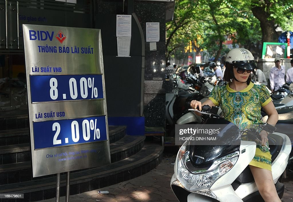 A customer leaves an outlet of the local commercial Bank for Investment and Development of Vietnam (BIDV) with saving interest rates offered for the local currency the dong (VND) at 8.00 % per year and US dollar at 2.00% per year in downtown Hanoi on May 10, 2013. Vietnam will cut interest rates for the eighth time in more than a year, hoping to improve the weakening economy, the central bank said on May 10. AFP PHOTO/HOANG DINH Nam.
