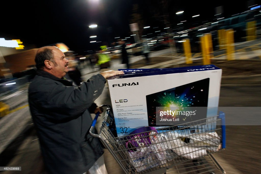 A customer leaves Wal-Mart with his purchased items Thanksgiving day on November 28, 2013 in Troy, Michigan. Black Friday shopping began early this year with most major retailers opening their doors on Thanksgiving day as consumers took advantage of discounted prices to prepare for the holiday season.